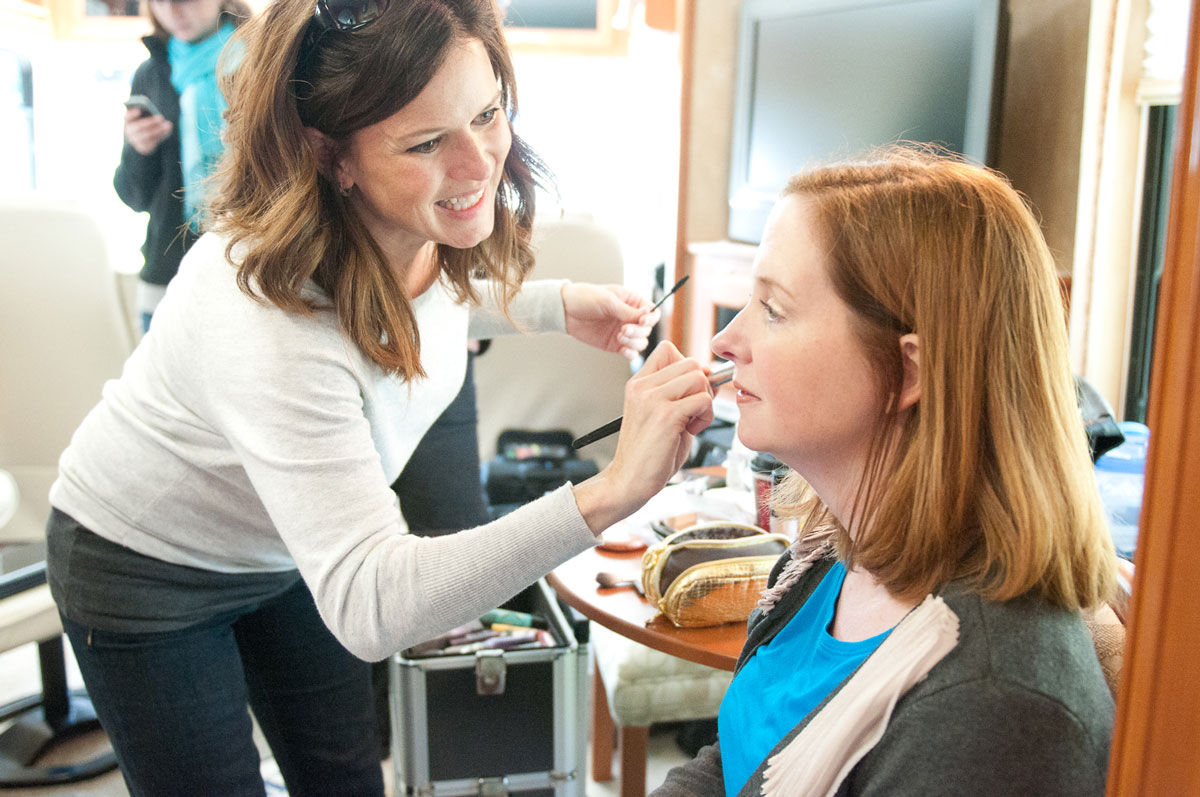 A commercial actor sits as makeup is applied by a crew member for a Red Noise 6 video production.