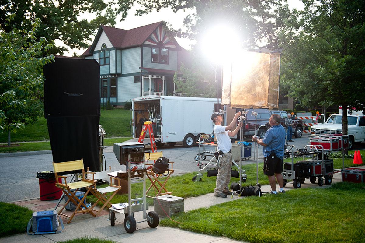 Video production crew members assemble lighting equipment on a sidewalk shoot.