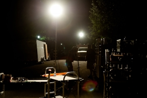 Bright lights are assembled in a dark and shadowed space in preparation for video production.
