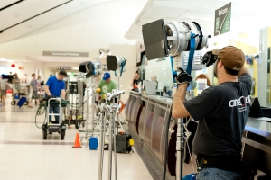 A Red Noise 6 production crew sets up lights in an airport in preparation for a video production.