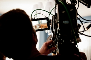 A camera operator looks through the viewfinder into a living room scene, where a couch and fooseball table sit.