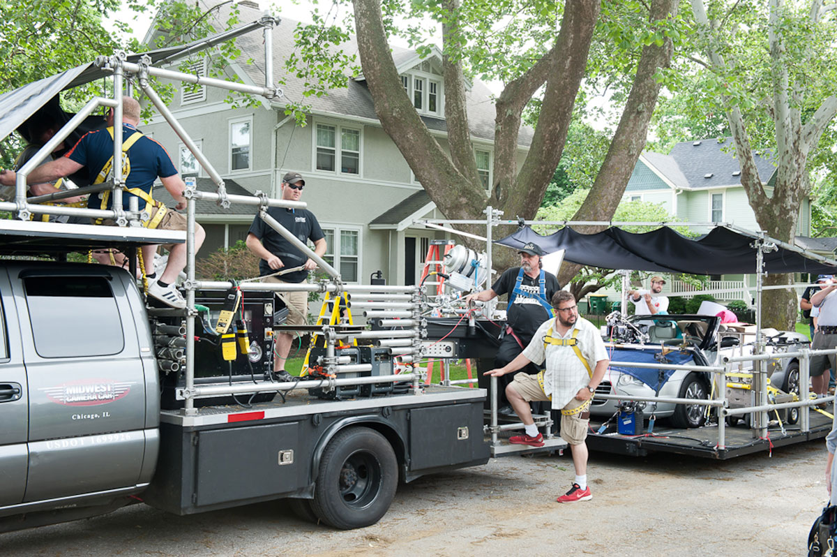 A production crew works on a truck equipped with production equipment.