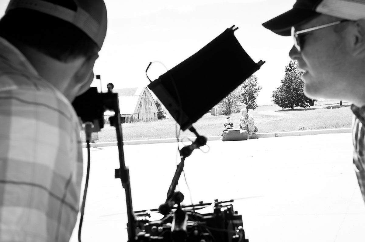 Video production experts view a scene through cameras of a man and young boy sitting on a curb.