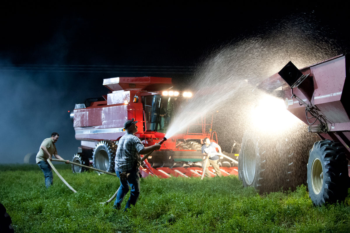A spray of water rushes out of a firehouse and onto a tractor as part of a video production.