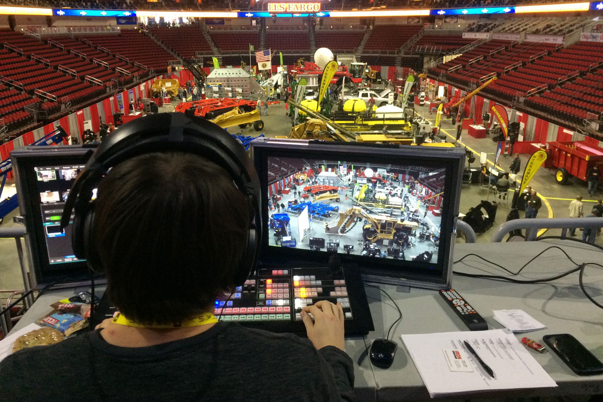 A Red Noise 6 employee sits behind two computer monitors as he live broadcasts an event in Wells Fargo Arena.