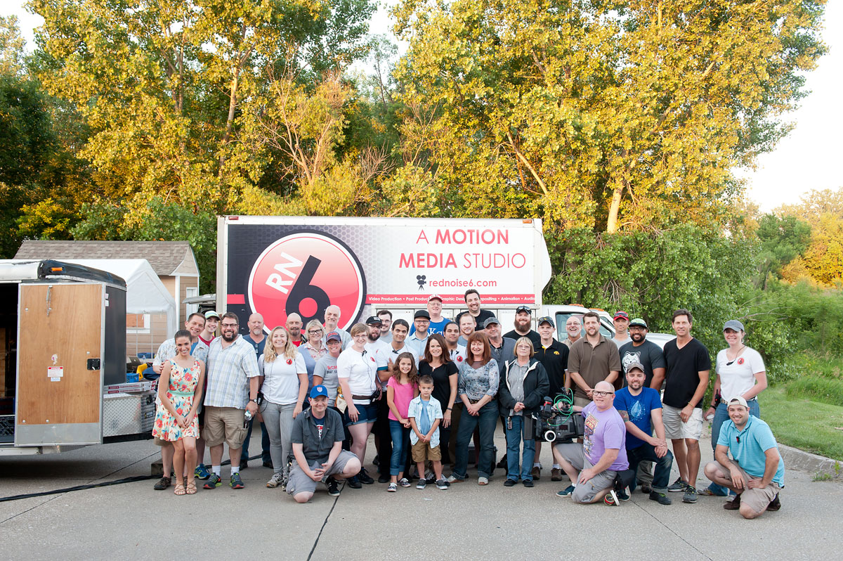 A group of extra hired hands provided by Red Noise 6 gathers for a group picture on a production set.